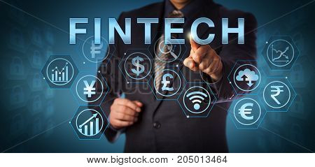 Unrecognizable business services manager touching FINTECH on an interactive screen. Business metaphor and computing concept for financial technology and mobile banking and investing via internet.