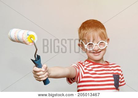 Boy Is Playing In The House Painter. Portrait. Roller For Painting