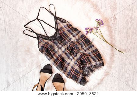 Checkered Top, Black Shoes And Wild Flowers. Fashionable Concept On White Fur