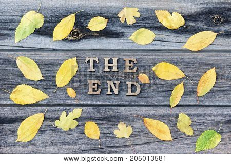 Inscription The End On A Wooden Background, Frame Of Yellow Leaves