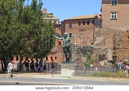ROME, ITALY - JULY 17, 2017: Tourists and bronze statue of emperor Caesar Augustus on Via dei Fori Imperiali near Roman Forum, Rome, Italy.