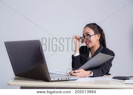 Businesswoman Sitting At Desk And Hand Holding Glasses In Office.