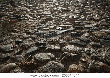 Closeup view on the road pavement bricks. Old cobblestone walkway. Morning time