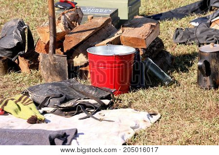 Bright red bucket sitting in the middle of a Civil War reenactment camp. poster
