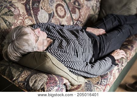 A Senior woman relaxing on sofa in the living room