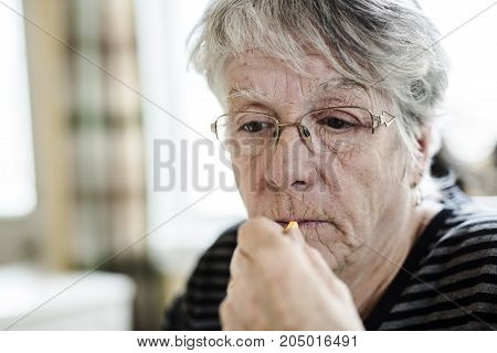 A Sick senior woman taking her pills at home