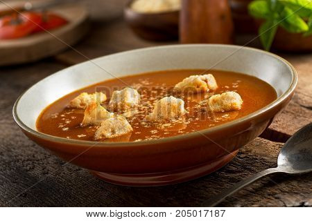 A delicious bowl of homemade rustic tomato soup with croutons and parmesan cheese.