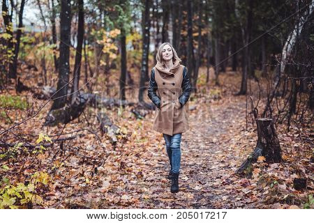 A woman walking through the countryside in autumn time