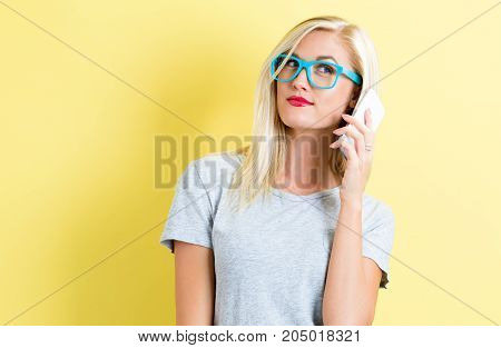 Young woman talking on the phone on a yellow background