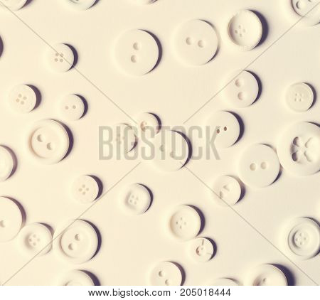 Scattered white buttons flat lay overhead view on white