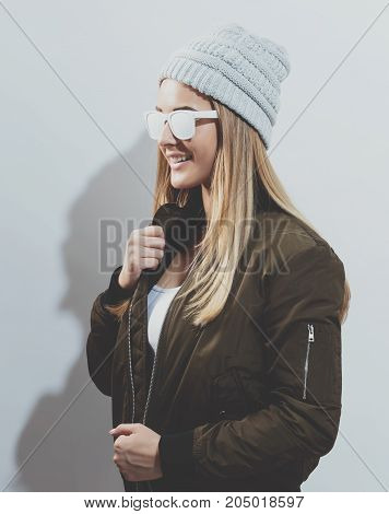 Hipster girl wearing sunglasses and hat on a white background