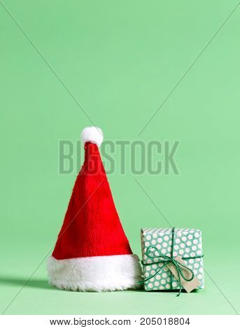 Christmas gift box with santa hat on a green background