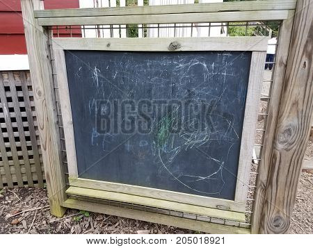 a blackboard or chalkboard with scribbles on it outside