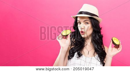 Happy young woman holding avocado halves on a pink background