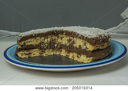 Coconut chocolate cake on blue dish with chocolate cream