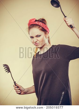 Disagreement in cooking. Kitchen accessories equipment in move. Girl having argument fight. Expression of anger.