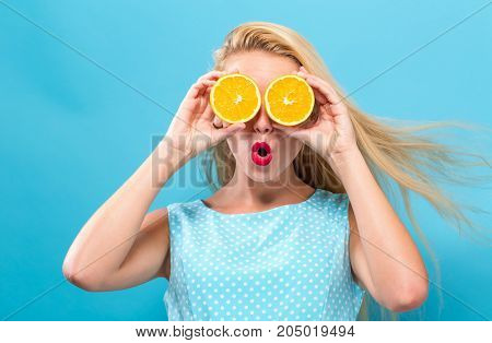 Happy young woman holding oranges on a solid background