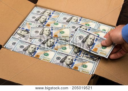 A man placing a hundred dollar bill in a box to send out