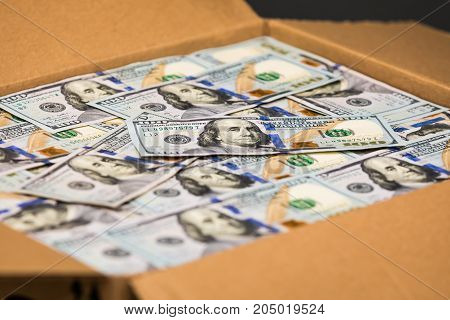 Some hundred dollar bills in a box ready to send