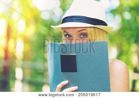 Young woman reading a book outside on a beautiful summer day