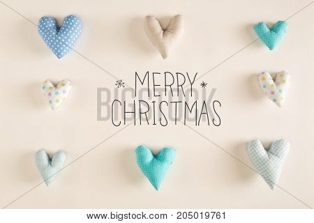 Merry Christmas message with blue heart cushions on a white paper background