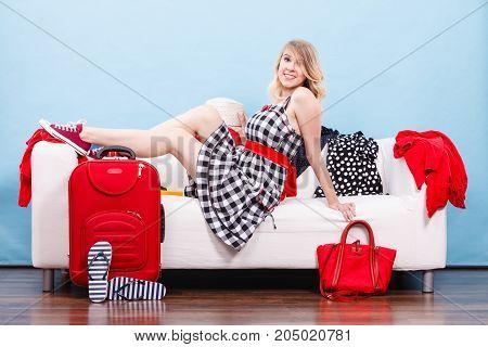 Traveling waiting for adventure concept. Woman relaxing lying on sofa after packing clothes into her red suitcase. Indoor shot