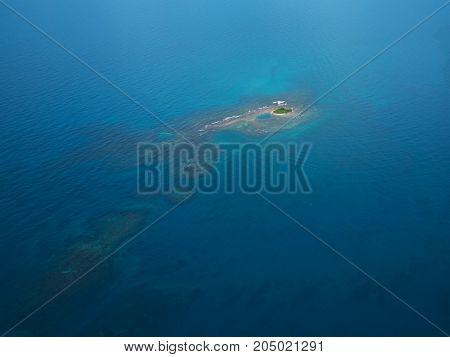 Small green island around blue sea water