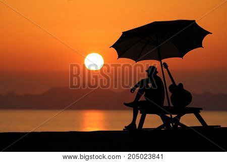 Silhouette of a man playing a guitar on the beach Red sky sunset background.