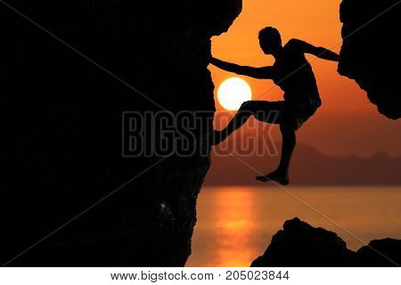 Silhouette of climber on a cliff against beautiful red sky sunset and the ocean.