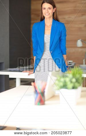 Portrait of a beautiful business woman standing near her workplace.
