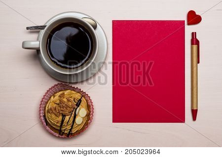 Coffee cup sweet cake cupcake and red paper blank with pen on wooden surface top view copy space for text