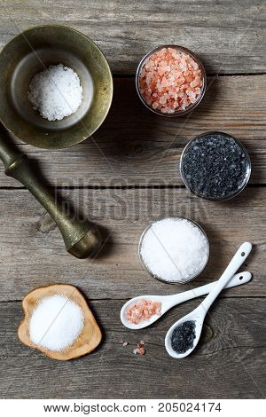 Salt of different types - sea, black, himalayan in glass saltcellars on a gray wooden background, space for text