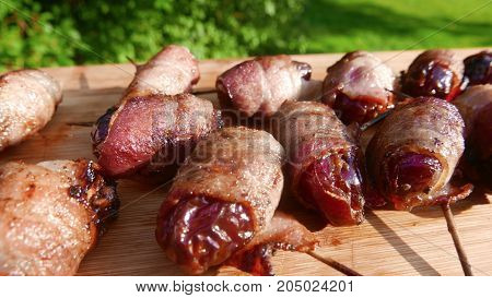 Smoked, bacon-wrapped appetizers on a picnic table
