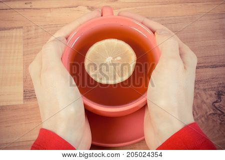Vintage Photo, Hand Of Woman Holding Cup Of Hot Tea On Wooden Table