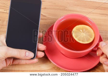 Hand Of Woman Touching Blank Screen Of Mobile Phone, Relax With Cup Of Tea