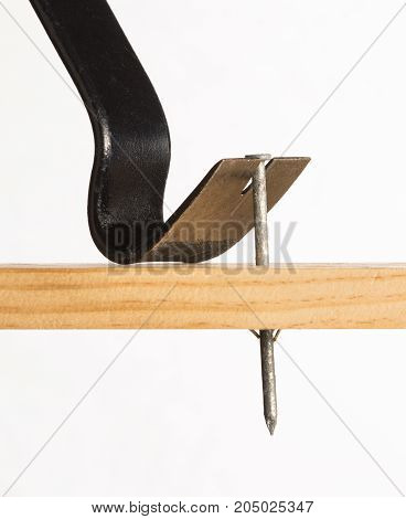 A pry bar is shown removing a large galvanized nail from a piece of wood