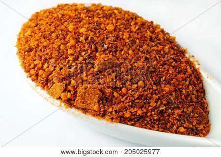 A close up of red chili powder in a white spoon isolated on white background.