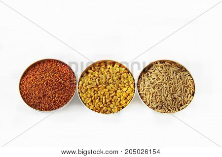 Three steel bowls with cumin fenugreek seeds cumin seeds and mustard seeds on white