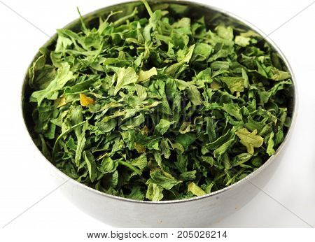 Close up of dried Parsley leaves on a white spoon isolated on white background.