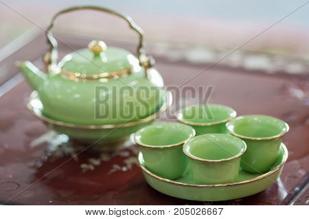 an Oriental teapot and four cups on table