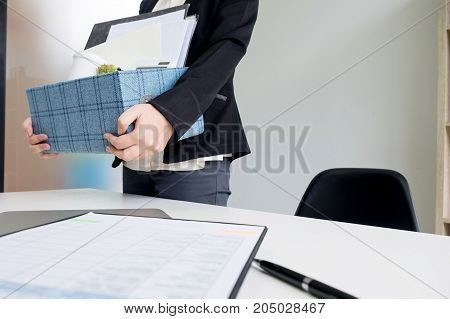 business woman packing personal company belongings when she deciding resignation and changing work in future.
