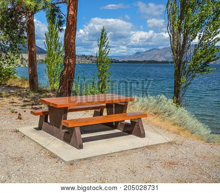 Picnic area with table and benches on a shore of Okanagan lake