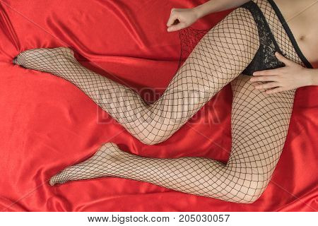 Woman in black stockings in a grid with related strap belt and necklace hands on red fabric