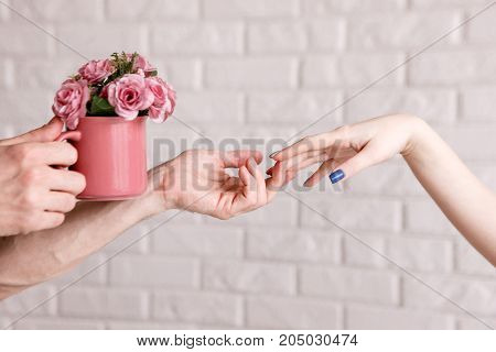 Man presenting beautiful roses in crimson cup to woman. Sensitive background with free space, gift with love, romantic proposal, start of relationship concept