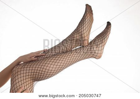 Sexy slender girl with beautiful legs in pantyhose mesh and black lacy panties over white background