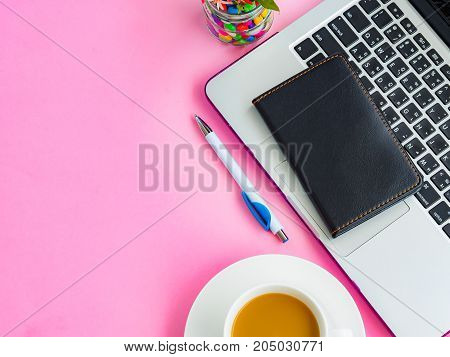 Top view feminine desk workspace with office accessories including laptop note book white pen and coffee cup on pink background.