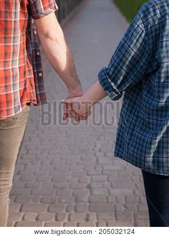 Strong romantic bound. Couple holding hands. Unrecognizable people outdoors, love connection background in focus on foreground. Gentle touch, road to future, tenderness concept