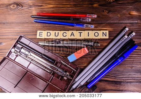 Case Of Drawing Instruments, Pencils And Eraser On Wooden Table. Education Inscription. Top View
