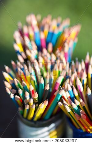 pencils in pencil holder on grass - stock image