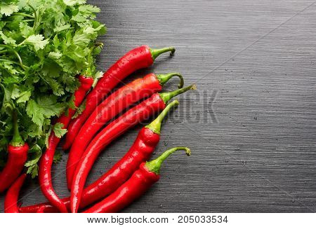 Red cayenne peppers (Capsicum annuum) and verdure on wooden table. Top view. Also known as Guinea spice, cow-horn pepper, red hot chili pepper, aleva, bird pepper.